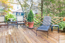 Closeup Of Wooden Deck Of House With Many Green Plants, Trees, Tables, Chairs, On Rainy Overcast Day, Decorations