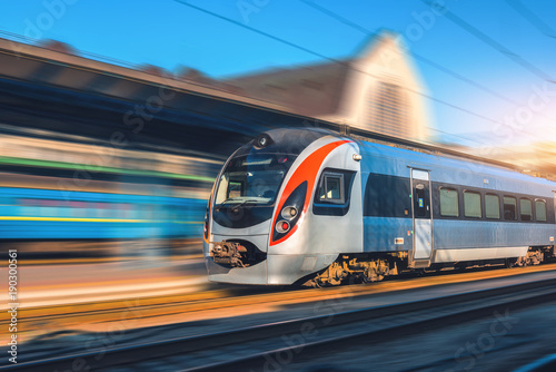 Fototapeta High speed train in motion at the railway station at sunset in Europe. Modern intercity train on the railway platform with motion blur effect. Industrial scene with moving passenger train on railroad obraz na płótnie