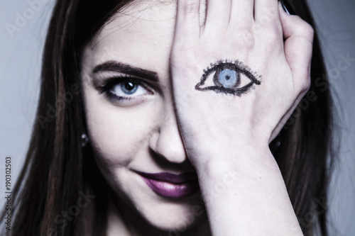 Staring brunette woman with painted eyes on her hand as a symbol of