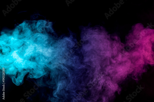Dense multicolored smoke of red, purple and pink colors on a black isolated background. Background of smoke vape