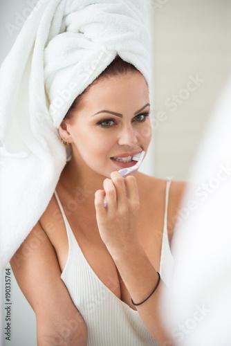 Fototapeta Pretty young woman brushing teeth in bathroom obraz na płótnie