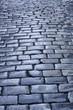 Antique wet cobblestone street at dawn. Vintage background. Blue tone