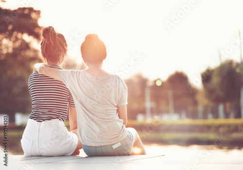 canvas print motiv - Fluky : Two women friends resting in the garden, watching the sunshine together happily.