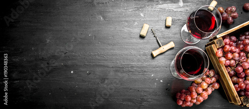 Photo Stands Wine Wine background. Red wine in an old box with a corkscrew.