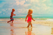 little boy and girl play with water on beach