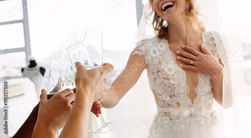 Bride with friends drinking champagne in bridal boutique Fototapete