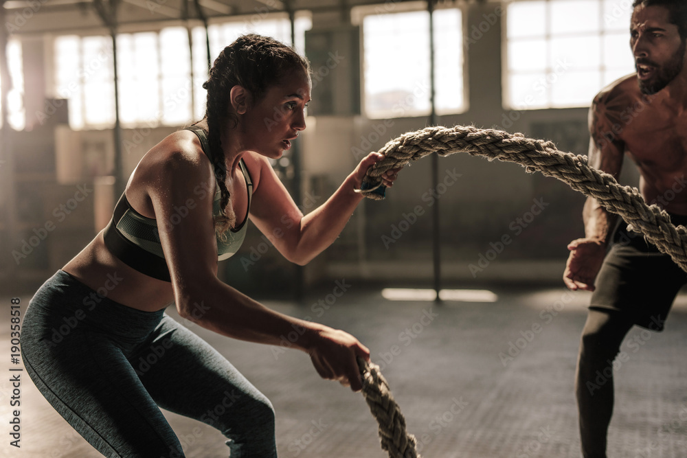 Fototapety, obrazy: Young woman working out with battle ropes