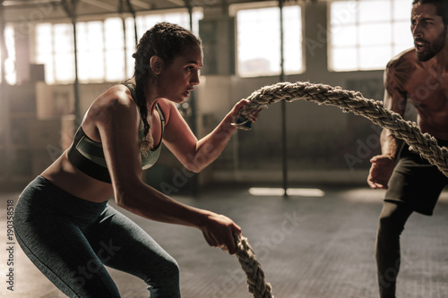 Fototapeta Young woman working out with battle ropes