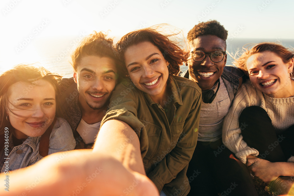 Fototapeta Cheerful friends taking selfie on a holiday
