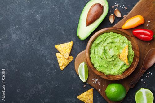 Pinturas sobre lienzo  Guacamole dip with avocado, lime and nachos on black table top view