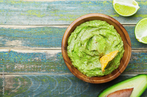 Fotografie, Obraz  Green guacamole with  ingredients avocado, lime and nachos on wooden vintage table top view