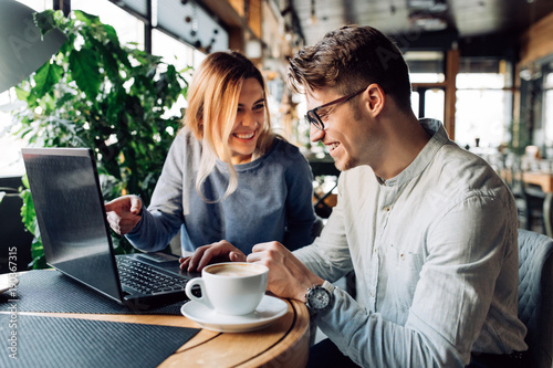 Fotografía  Attractive man in eyeglasses and charming woman is pointing at the laptop screen, laughing together, resting at cafe with cup of coffee