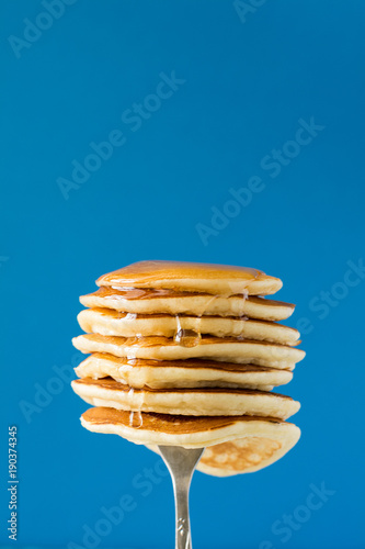 Stack of pancakes with honey decorated sweet cherry pinned on a fork on blue background