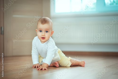 In de dag Retro Adorable little baby sitting in bedroom on the floor with bottle with milk or water and laughing. Infant Childhood Kids People concepts. Cozy home with children Lifestyle