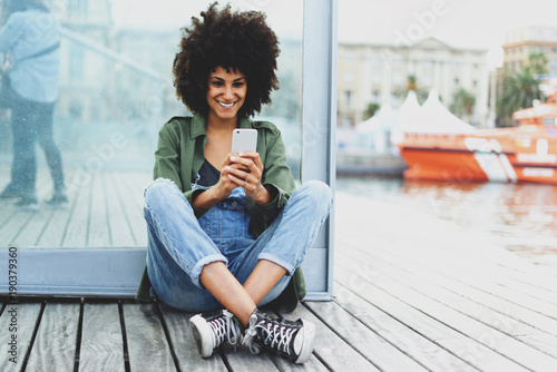 a dark-skinned beautiful girl with afro hair talking through a webcam with her friends. young female student watching a video lesson while sitting on a wooden embankment cover