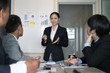 businesswoman present financial plan report to co worker team. woman leader discuss sales data with investor colleagues. finance investment business meeting