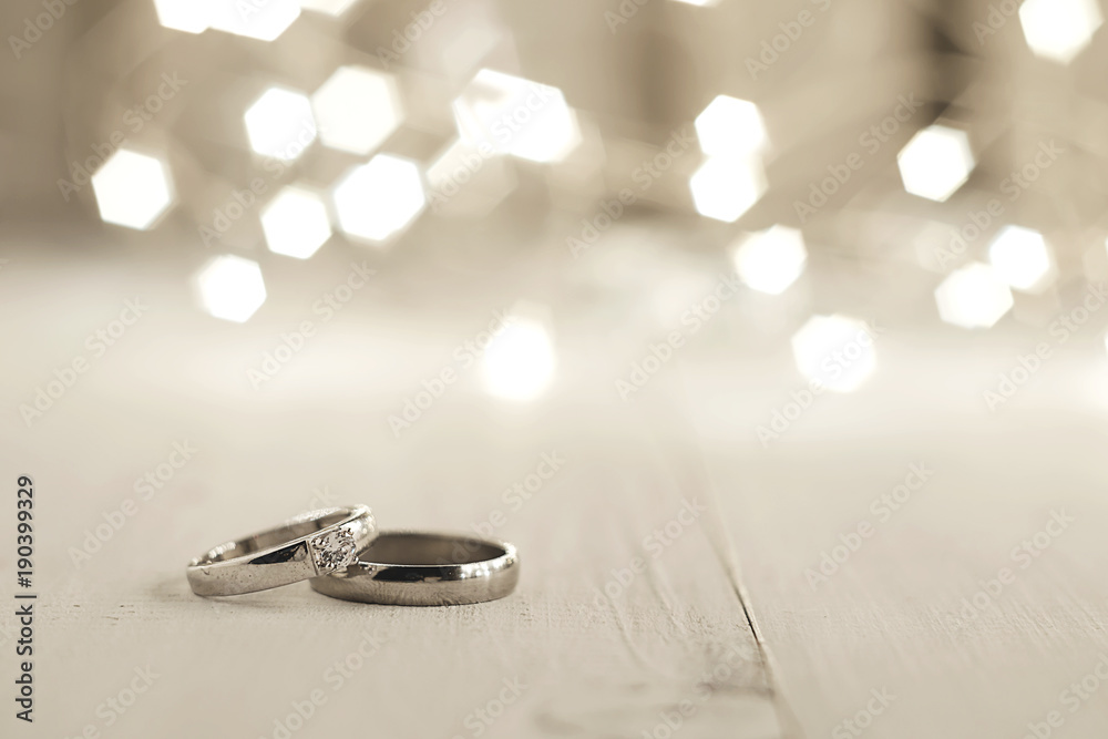 Fototapety, obrazy: Two wedding rings place on wooden floor with light bokeh background.