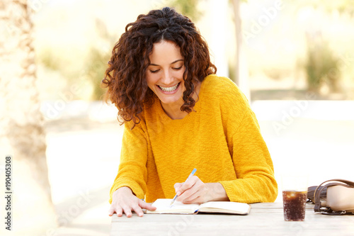 Obraz young woman sitting at table writing in diary - fototapety do salonu