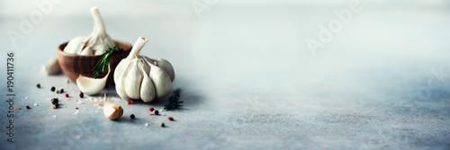 Fotografie, Obraz  Garlic, rosemary, black pepper, salt on grey concrete background