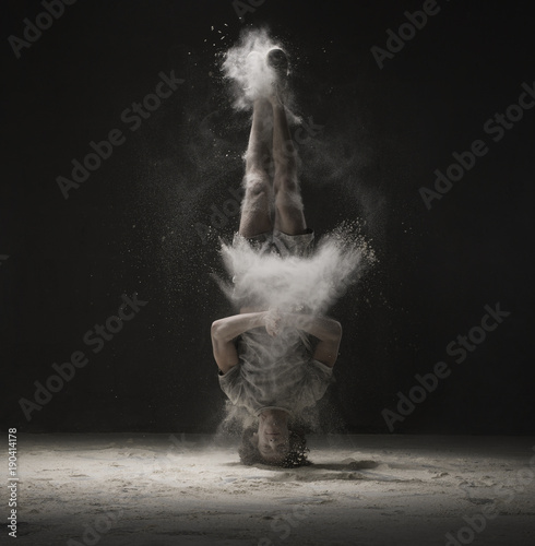 Young dancer doing a headstand in dust cloud view Canvas-taulu