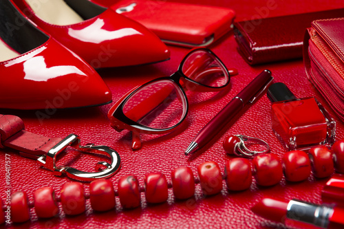 Red woman accessories, jewelry, cosmetic, shoes and other luxury objects on leather background, fashion industry, modern female concept, selective focus