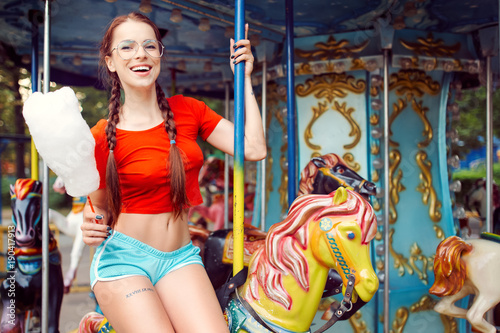 Foto  Young beautiful sexy woman in a red vest with pigtail glasses blue shorts white
