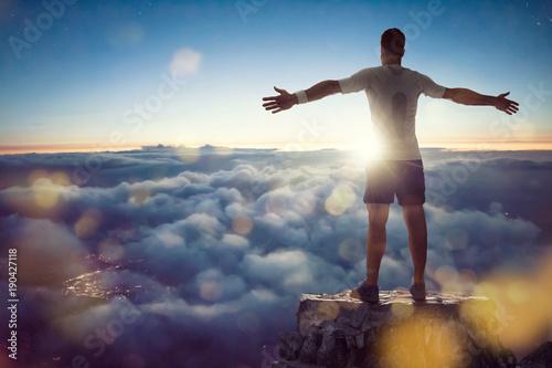 Obraz Mann über den Wolken breitet Arme aus - fototapety do salonu