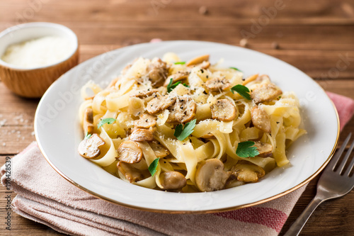 Tagliatelle pasta with mushrooms, parsley and Parmesan cheese on wooden table Fototapeta