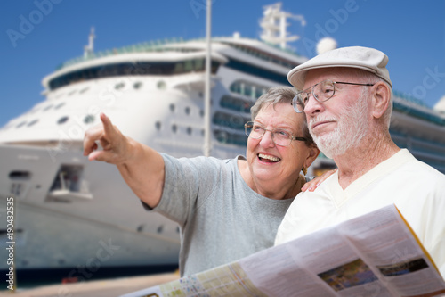 In de dag Schip Happy Senior Adult Couple Tourists with Brochure Next To Passenger Cruise Ship.