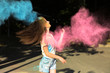 Happy young woman with wind in hair playing with blue and pink dry paint Holi