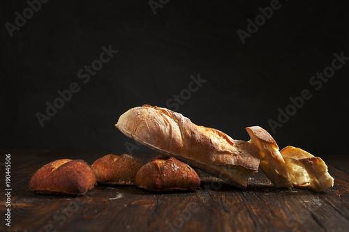 In de dag Bakkerij freshly baked bread on a wooden table on a dark background