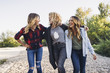 Happy female friends walking on pebbles against clear sky