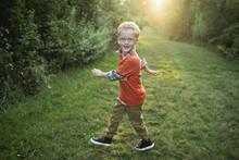 Portrait Of Smiling Boy Walkin...