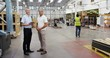 4k, Warehouse manager and a businessman using digital tablet in busy warehouse. Slow motion.