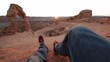 Handheld shot of hiker sitting on rocks against clear sky at Arches National Park