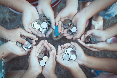 Fotografie, Obraz  Group of children holding money in hands in the circle together as finance and c