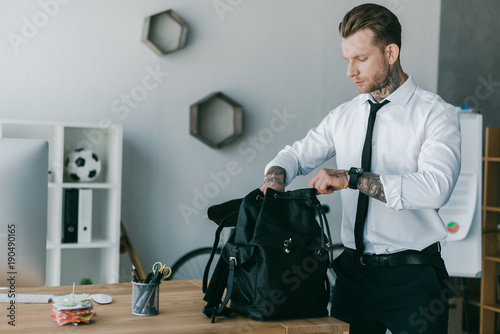 handsome young tattooed businessman opening backpack at workplace Wallpaper Mural