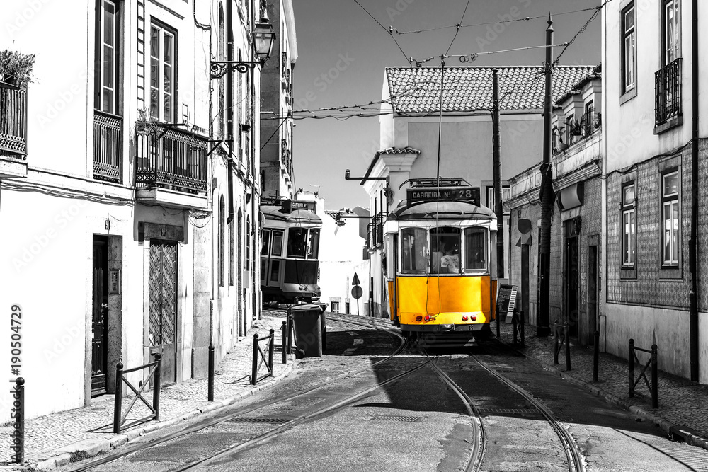 Fototapeta Yellow tram on old streets of Lisbon, Portugal, popular touristic attraction and destination. Black and white picture with a coloured tram.