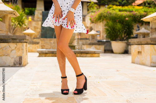 Woman with slim sexy legs posing in white summer dress and black high heels