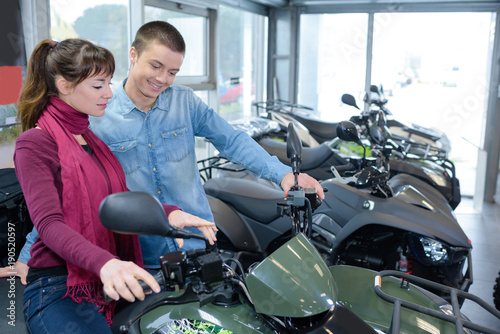 Young couple looking at quad bikes