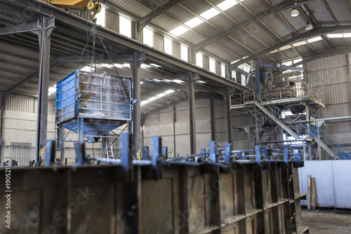 Concrete deposit filling iron mold structure to create construction concrete pieces