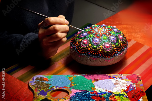 Drawing with a brush a mandala on a stone Canvas Print