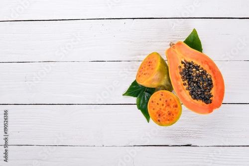Fototapeta Papaya and cactus fruit. Fresh Tropical Fruits. On a wooden background. Top view. Copy space. obraz na płótnie
