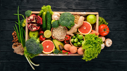 The concept of healthy food. Fresh vegetables, nuts and fruits in a wooden box. On a wooden background. Top view. Copy space.