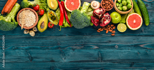 Healthy food background. Concept of Healthy Food, Fresh Vegetables, Nuts and Fruits. On a wooden background. Top view. Copy space. © Yaruniv-Studio