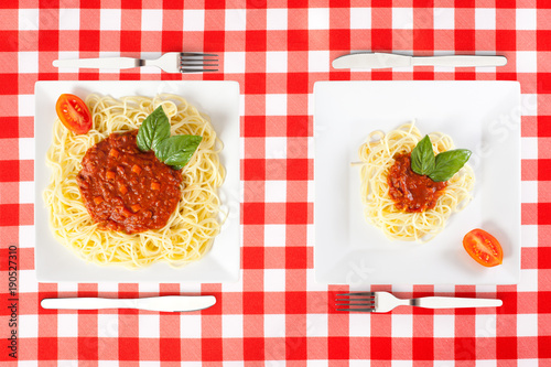 Fototapeta Contrasting large and tiny food portions of Spaghetti obraz