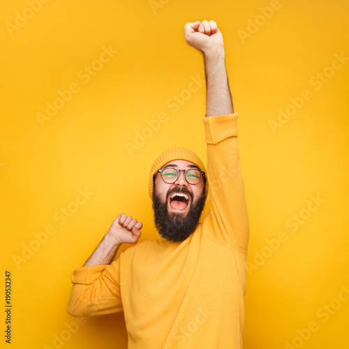 Photo  Celebrating bearded man with hand up
