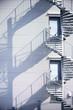 canvas print picture - Notausgänge mit Wendeltreppe  / Eine Wendeltreppe, Feuerleiter, an der Seitenfassade eines Industriegebäudes wirft Schatten.