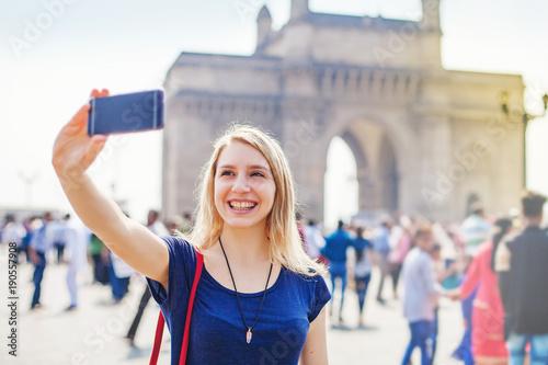 Foto Caucasian woman posing in front of Gateway of India in Mumbai and taking selfie
