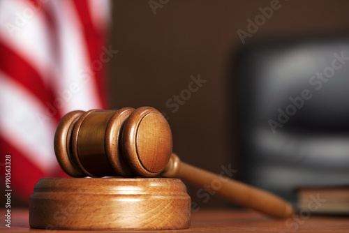 Wooden gavel on the table of judge with american flag and black chair Wallpaper Mural
